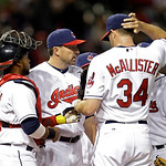 Cleveland Indians pitching coach Mickey Callaway, center, pays a visit to starting pitcher Zach McAllister (34) on the mound as catcher Carlos Santana listens, left, in the fifth inning of a …
