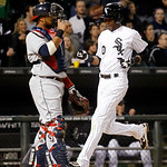 Chicago White Sox's Alexei Ramirez, right, scores past Cleveland Indians catcher Carlos Santana off a double by Hector Gimenez during the fourth inning of a baseball game, Monday, April 22,  …