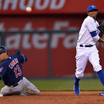 Cleveland Indians' Asdrubal Cabrera (13) is out at second and looks back as Kansas City Royals shortstop Alcides Escobar throws out Cleveland Indians' Nick Swisher at first for a double play …