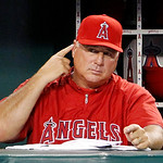 Los Angeles Angels manager Mike Scioscia signals his players during a baseball game against the Cleveland Indians in Anaheim, Calif., Monday, Aug. 13, 2012. (AP Photo/Reed Saxon)