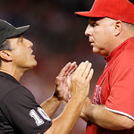 Los Angeles Angels manager Mike Scioscia argues with first base umpire Phil Cuzzi over an out call on a third-inning double play against the Cleveland Indians in a baseball game in Anaheim,  …