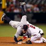 Cleveland Indians second baseman Jason Donald is upended but completes the double play on Los Angeles Angels' Erick Aybar at second and Chris Iannetta at first in the fifth inning of a baseb …