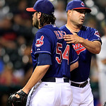 Cleveland Indians manager Manny Acta, right, pats pitcher Chris Perez on the back as Perez heads to the dugout in the ninth inning of a baseball game against the Minnesota Twins, Tuesday, Au …