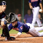 Cleveland Indians' Jason Kipnis, right, scores as Minnesota Twins catcher Joe Mauer waits for the ball in the sixth inning of a baseball game, Tuesday, Aug. 7, 2012, in Cleveland. (AP Photo/ …