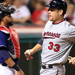 Minnesota Twins' Justin Morneau, right, scores in front of Cleveland Indians catcher Carlos Santana in the ninth inning of a baseball game, Tuesday, Aug. 7, 2012, in Cleveland. Morneau score …