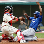 Kansas City Royals' Lorenzo Cain, right, scores ahead of the tag by Cleveland Indians catcher Carlos Santana in the second inning of a baseball game on Sunday, July 14, 2013, in Cleveland. C …