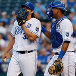 Kansas City Royals starting pitcher Luis Mendoza talks with Kansas City Royals catcher Salvador Perez, right, after walking in a run during the first inning of a baseball game against the C …