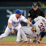 Cleveland Indians' Nick Swisher, right, slides safely as the ball gets past Kansas City Royals second baseman Johnny Giavotella, left, during the third inning of a baseball game at Kauffma …