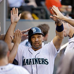 Seattle Mariners' Raul Ibanez is congratulated after scoring against the Cleveland Indians in a baseball game Tuesday, July 23, 2013, in Seattle. (AP Photo/Elaine Thompson)