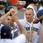 Seattle Mariners' Kyle Seager is congratulated after scoring against the Cleveland Indians in a baseball game Tuesday, July 23, 2013, in Seattle. (AP Photo/Elaine Thompson)