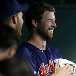 Cleveland Indians starting pitcher Corey Kluber smiles in the dugout after finishing out the eighth inning of a baseball game against the Texas Rangers on Tuesday, June 11, 2013, in Arlingto …