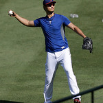 Texas Rangers pitcher Yu Darvish of Japan tosses a ball to fans during batting practice before a baseball game against the Cleveland Indians Wednesday, June 12, 2013, in Arlington, Texas. (A …