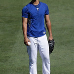 Texas Rangers pitcher Yu Darvish of Japan holds a ball in the outfield during batting practice before a baseball game against the Cleveland Indians Wednesday, June 12, 2013, in Arlington, Te …