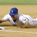 Texas Rangers designated hitter Lance Berkman slides head first into third base during the sixth inning of a baseball game against the Cleveland Indians Wednesday, June 12, 2013, in Arlingto …