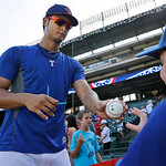 Texas Rangers starting pitcher Yu Darvish, left, of Japan, hands a ball to a fan after signing it during batting practice before a baseball game against the Cleveland Indians, Wednesday, Jun …