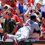 Cleveland Indians first baseman Carlos Santana falls into a fan trying to catch a foul ball hit by Cincinnati Reds' Todd Frazier in the fifth inning of a baseball game, Thursday, June 14, 20 …