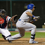 Kansas City Royals' David Lough bunts in front of Cleveland Indians catcher Carlos Santana in the ninth inning of a baseball game Monday, June 17, 2013, in Cleveland. Lough was safe at first …