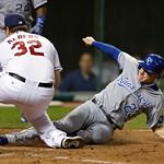 Kansas City Royals' Elliot Johnson, right,  slides home to score from third on a wild pitch by Cleveland Indians relief pitcher Matt Albers,left, who covered home plate on the play, in the n …