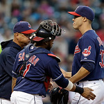 Cleveland Indians starting pitcher Ubaldo Jimenez, right, gets a pat from catcher Carlos Santana (41) as manager Terry Francona, left, removes him from a baseball game against the Kansas Cit …