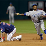 Kansas City Royals shortstop Alcides Escobar (2) throws to first over Cleveland Indians' Carlos Santana but to late to complete a double play on Michael Brantley in the seventh inning of a b …