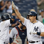 New York Yankees' Robinson Cano, left, greets Mark Teixeira at the plate after Teixeira hit a third-inning grand slam off Cleveland Indians starting pitcher Justin Masterson in a baseball ga …