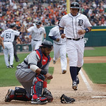 Cleveland Indians catcher Carlos Santana, left foreground, reaches for his mask as Detroit Tigers' Miguel Cabrera, right foreground, Prince Fielder, center, and Don Kelly head home after Kel …