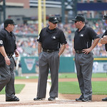 Umpires, from left, Rob Drake, Andy Fletcher, Sam Holbrook, and Joe West gather at home plate before the start of a baseball game between the Detroit Tigers and the Cleveland Indians in Detr …