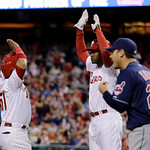 Philadelphia Phillies' Carlos Ruiz, left, and Domonic Brown celebrate after scoring on a double by John Mayberry Jr. as Cleveland Indians starting pitcher Scott Kazmir, right, walks to the m …