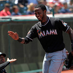 Miami Marlins' Jose Reyes smiles as he is greeted at the dugout after scoring on a sacrifice ground ball by teammate Hanley Ramirez against the Cleveland Indians in the first inning of an in …