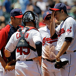 Cleveland Indians starting pitcher Jeanmar Gomez, right, wipes his brow as he is visited on the mound by, from left, Indians pitching coach Scott Radinsky, catcher Luke Carlin (45), and shor …
