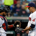 Cleveland Indians catcher Carlos Santana, lewft, delivers a new ball to starting pitcher Ubaldo Jimenez in the third inning of a baseball game Monday, May 6, 2013, in Cleveland. (AP Photo/Ma …