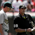Oakland Athletics manager Bob Melvin goes over a lineup change with home plate umpire Paul Nauert (39) in the seventh inning of a baseball game against the Cleveland Indians, Thursday, May 9 …
