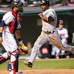 Chicago White Sox's Dewayne Wise, right, scores on a single by designated hitter Adam Dunn in the sixth inning of a baseball game against the Cleveland Indians, Monday, Oct. 1, 2012, in Clev …