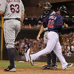 Minnesota Twins' Alexi Casilla scores on teammate Justin Morneau's sacrifice fly against Cleveland Indians starting pitcher Justin Masterson (63) during the fourth inning of a baseball game, …