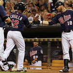 Minnesota Twins' Alexi Casilla (12) is congratulated by teammate Ryan Doumit (18) after scoring on teammate Justin Morneau's sacrifice fly against Cleveland Indians starting pitcher Justin M …
