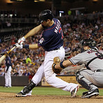 Minnesota Twins' Joe Mauer (7) hits an RBI single against Cleveland Indians relief pitcher Scott Maine as Indians catcher Lou Marson looks on during the seventh inning of a baseball game, Mo …