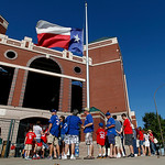 A Texas flag flies at half staff as fans line up to enter the Texas Rangers Ballpark in Arlington before a baseball game against the Cleveland Indians Tuesday, Sept. 11, 2012, in Arlington,  …