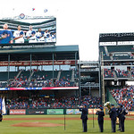 The Texas Rangers are shown on a large video screen at the top of the ballpark as the U.S. Air Force honor guard and band participate in a Sept. 11, 2001 terrorist attack pregame ceremony be …