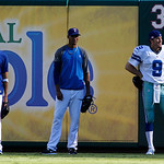 Texas Rangers relief pitcher Mike Adams, left, smiles as he and Alexi Ogando, center, stand by closer Joe Nathan, right, wearing a Dallas Cowboys Tony Romo uniform during batting practice be …