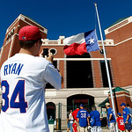 Robert Gallagher, of Fort Worth, Texas, takes a photo of the Texas flag at half staff with his smartphone as he and other fans wait for the gate to open for a baseball game between the Cleve …