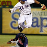 Texas Rangers shortstop Elvis Andrus leaps over Cleveland Indians' Jason Kipnis after getting the force on Kipnis on a fielders choice by Carlos Santana in the eighth inning of a baseball ga …