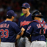 Cleveland Indians pitching coach Ruben Niebla (33) talks to starting pitcher Ubaldo Jimenez, center, and catcher Carlos Santana, right, during a baseball game against the Texas Rangers  Tues …