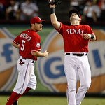 Texas Rangers first baseman Mitch Moreland, right, reaches up for a fly-out by Cleveland Indians' Carlos Santana in the fifth inning of a baseball game as second baseman Ian Kinsler, rear, w …