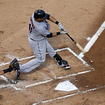 Cleveland Indians catcher Carlos Santana (41) connects at the plate as Texas Rangers catcher Geovany Soto, watches during a baseball game Thursday, Sept. 13, 2012, in Arlington, Texas. The I …