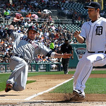 Cleveland Indians' Jason Kipnis slides safely into home plate to score as Detroit Tigers starting pitcher Anibal Sanchez, right, covers on a passed ball in the first inning of a baseball gam …