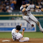 Cleveland Indians shortstop Asdrubal Cabrera jumps away from Detroit Tigers' Don Kelly (32), while watching his throw to first to complete the double play on Alex Avila during the fifth inni …