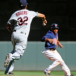 Cleveland Indians pitcher Esmil Rogers, left, runs down and tags out Minnesota Twins center fielder Ben Revere, right, as Revere is caught between second and third base in the seventh inning …