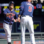 Minnesota Twins first baseman Justin Morneau, left, celebrates with third base coach Steve Liddle, right, after hitting a two-run home run against Cleveland Indians pitcher Corey Kluber in t …