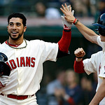 Cleveland Indians' Mike Aviles is congratulated by teammates after hitting a two-run home run in the eighth inning of a home opener baseball game against the New York Yankees on Monday, Apri …