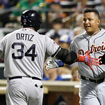 American League's Miguel Cabrera, of the Detroit Tigers, is congratulated by David Ortiz, of the Boston Red Sox, after scoring on Toronto Blue Jays' Jose Bautista's sacrifice fly during th …